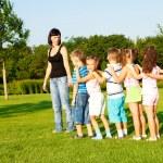 Preschool boys and girls with teacher — Stock Photo