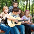 Teenagers in park playing guitar — Foto de Stock