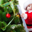 Royalty-Free Stock Photo: Baby in Santa costume on a step ladde