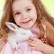 Girl holding white rabbit — Stock Photo