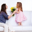 Kid presenting flowers to mother — Stock Photo