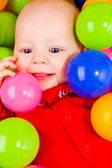 Cheerful baby with balls — Stock Photo