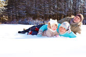 Parents and their daughter lying in snow — Stock Photo