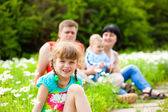 Girl in the meadow and her family — Stock Photo