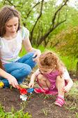 дочь помогая мама в саду — Стоковое фото