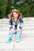 Girl sitting on stairs — Stock Photo
