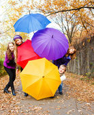 Friends hiding behind umbrellas — Stock Photo