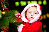Baby decorating Christmas tree — Stock Photo