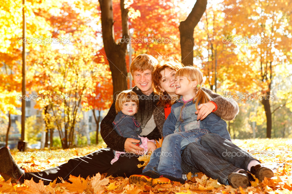 Young family in autumn park lying on yellow leaves — Stock Photo #5770464