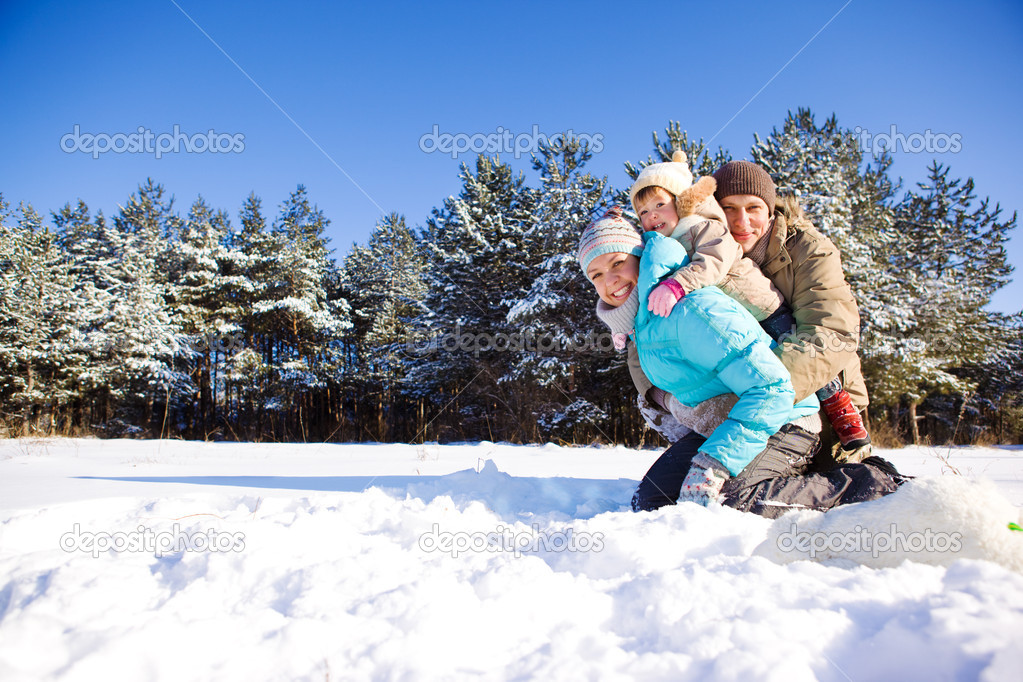 Toddler girl and her parents in a snowy park — Stock Photo #5771528