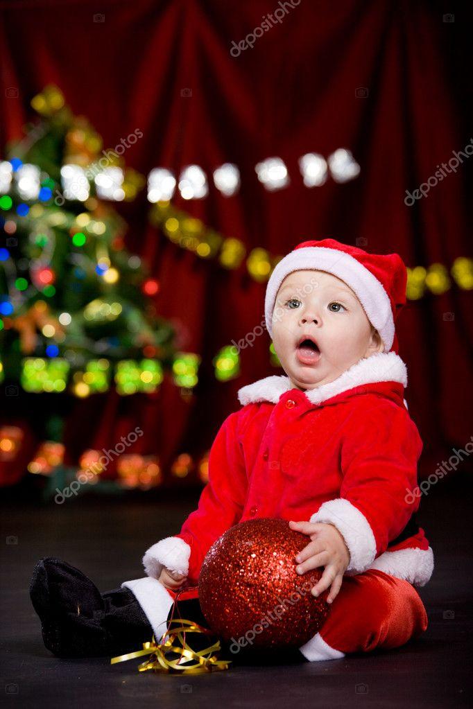 Surprised toddler having large Christmas ball in hands — Stock Photo #5775369