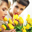 Two flower nymphs and a bunch of tulips — Stock Photo