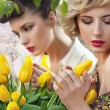 Two beautiful ladies in a tulip garden — Stok fotoğraf