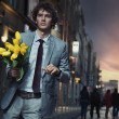 Elegant man holding flowers — Stock Photo #5489597