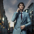 Elegant man posing on a city street - Stock Photo