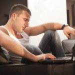 lächelnd junger mann arbeitet am laptop zu hause — Stockfoto