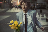Attractive guy with bunch of tulips — Stock Photo