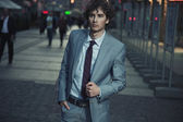 Handsome guy walking on a evening city street — Stock Photo