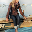 Girl sitting on a pier - Stock fotografie