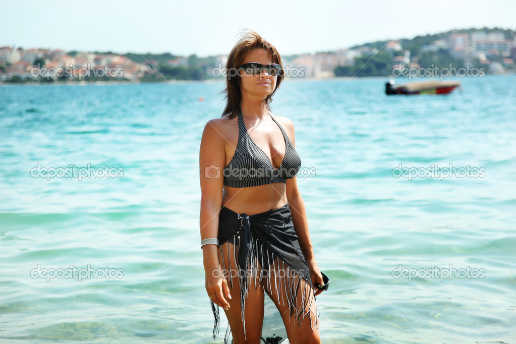 Woman standing on a beach and enjoying the sun — Stock Photo #5608714