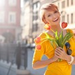 Smiling woman with bunch of flowers — Stockfoto