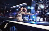 Smiling couple over night city background — Stock Photo