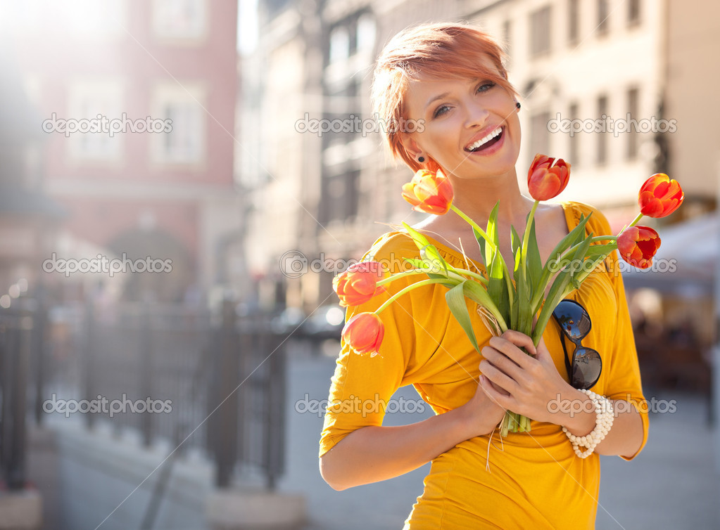 Smiling woman with bunch of flowers — Zdjęcie stockowe #5620700