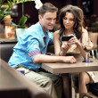Стоковое фото: Cute womshowing something to her boyfriend on phone