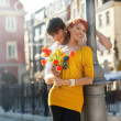 Young couple with flowers, outdoors — Stockfoto