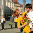 Woman holding flower bouquet smiling at man. — Stock Photo