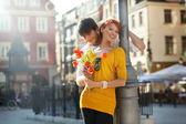 Młoda para z kwiatami, na zewnątrz — Zdjęcie stockowe