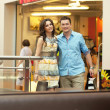 Foto Stock: Young handsome couple having fun at shopping center