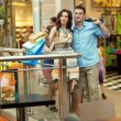 Foto de Stock  : Young handsome couple having fun at shopping center