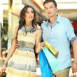 Young couple having fun in a shopping center — Stock Photo