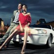 Stock Photo: Sexy young couple in front of limousine