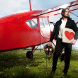 Young handsome man posing next to aeroplane - Stock Photo
