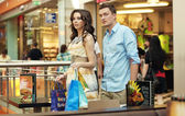 Young handsome couple walking at shopping passage — Stock Photo