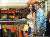 Young couple walking at shopping passage — Stock Photo