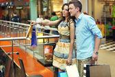 Jonge vrouw weergeven met iets bij het shopping center — Stockfoto