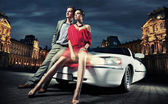 Sexy young couple in front of a limousine — Foto de Stock