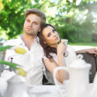 Young couple enjoying coffee in the garden - Stock Photo