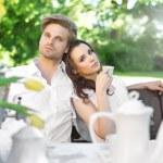 Young couple enjoying coffee in the garden — Stock Photo