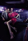 Knappe paar knuffelen in een luxe limousine — Stockfoto