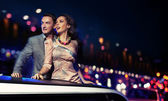 Elegant couple traveling a limousine at night — Stock Photo
