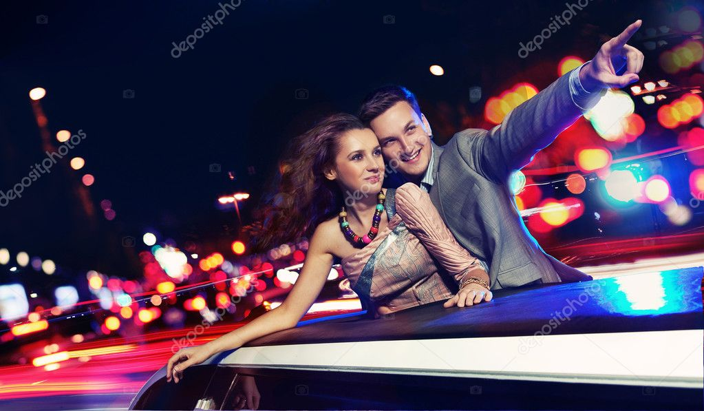 Elegant couple traveling a limousine at night — Stock Photo #5827320