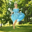 Young charming laughing woman in beautiful dress jumps on meadow — Stockfoto #6018808