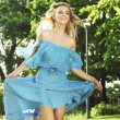Young woman in blue dress jumping over green grass — Stockfoto