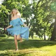 Young woman in blue dress jumping over green grass — Photo