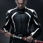 Handsome man holding a samurai sword — Stock Photo