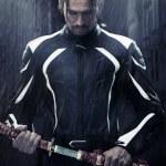 Muscular man holding samurai sword in on a rainy night — Stock Photo